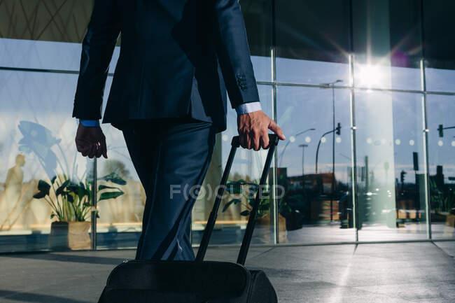 Businessman with wheeled luggage walking towards glass building, Malpensa, Milan — Stock Photo