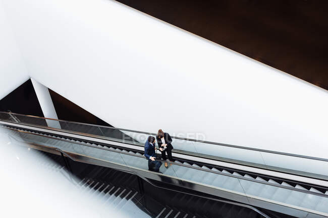 Businessman and businesswoman with wheeled luggage on escalator in hotel building — Stock Photo