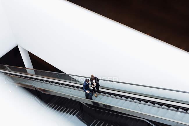 Homme d'affaires et femme d'affaires avec bagage à roues sur escalator dans le bâtiment de l'hôtel — Photo de stock