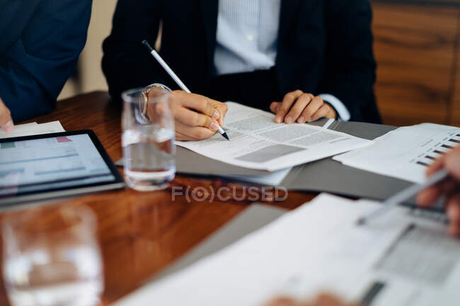 Businessmen and woman at boardroom table working on paperwork, cropped — Stock Photo