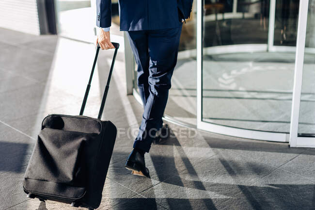 Businessman with wheeled luggage entering revolving doors of building — Stock Photo