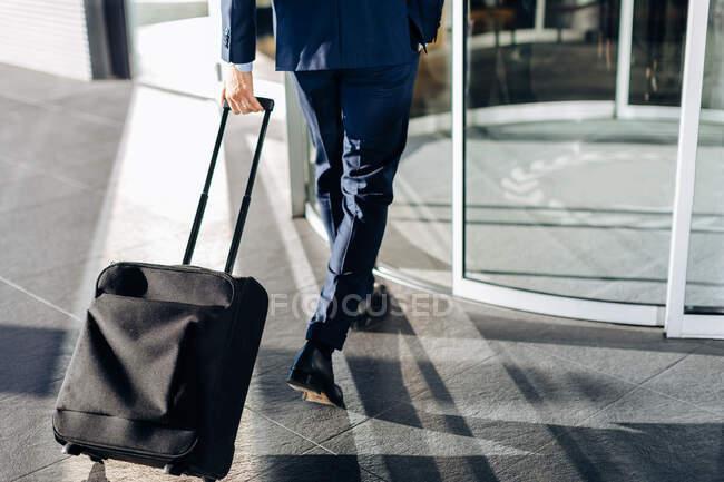 Бизнесмен с колесным багажом входит в вращающиеся двери здания — стоковое фото