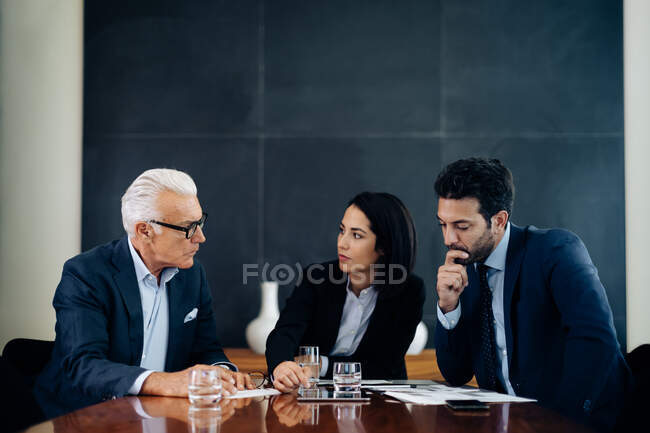 Businessmen and woman having discussion at boardroom table — Stock Photo