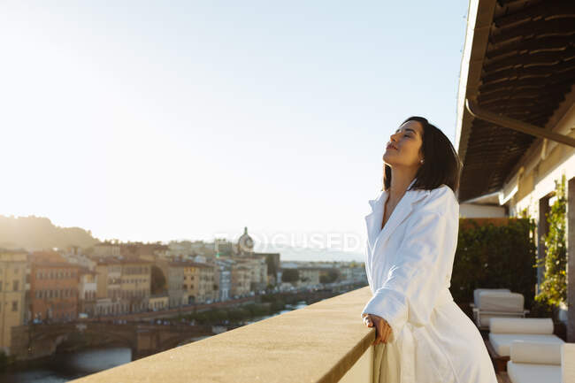 Donna che gode del sole sul balcone dell'hotel, Firenze, Toscana, Italia — Foto stock