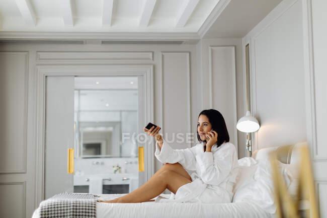 Donna con smartphone e telecomando in suite — Foto stock