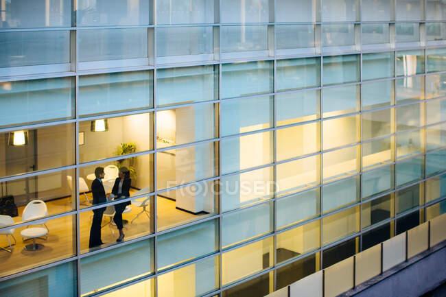 Homme d'affaires et femme d'affaires discutant par fenêtre — Photo de stock
