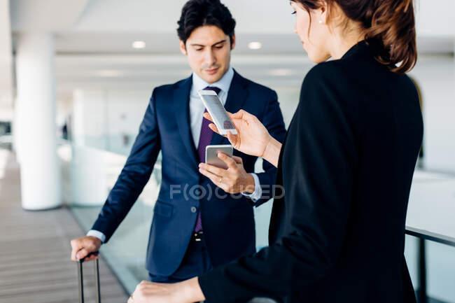 Uomo d'affari e donna d'affari con bagaglio a ruote utilizzando i telefoni cellulari nell'edificio dell'hotel — Foto stock