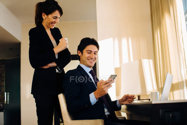Businessman and businesswoman sharing text message in hotel room — Stock Photo