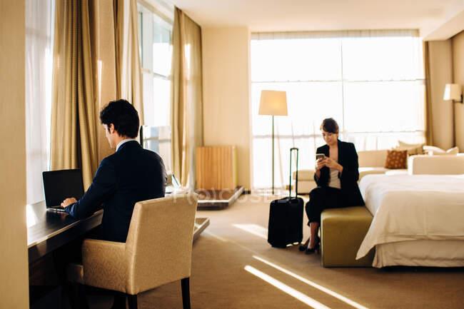 Empresario y mujer de negocios trabajando en el dormitorio del hotel - foto de stock