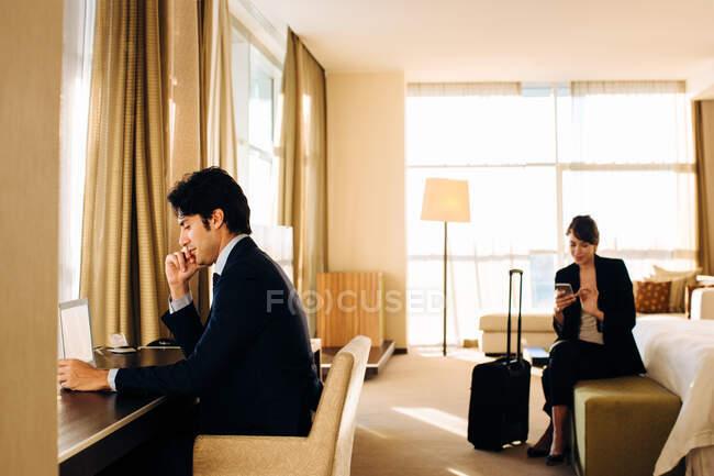 Uomo d'affari e donna d'affari che lavorano nella camera da letto dell'hotel — Foto stock