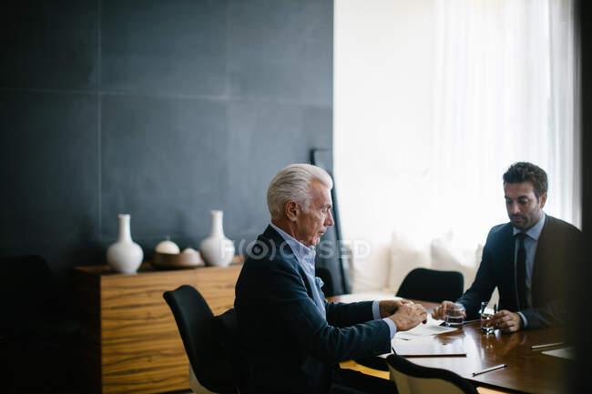Deux hommes d'affaires réunis à la table du conseil d'administration — Photo de stock