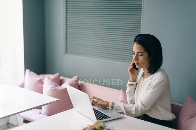 Young businesswoman at hotel table looking laptop and using smartphone — Stock Photo