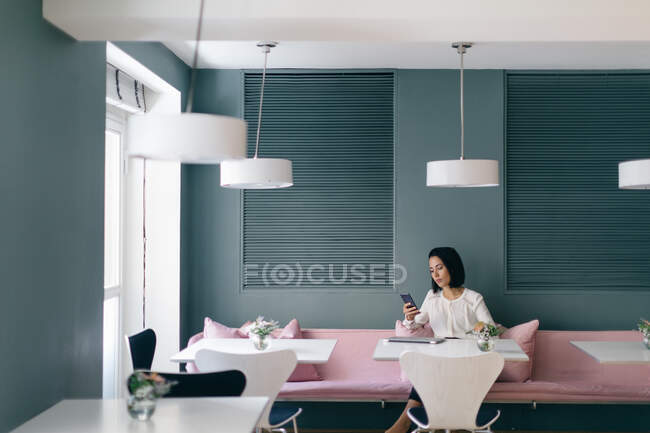 Young businesswoman at hotel table looking at smartphone — Stock Photo