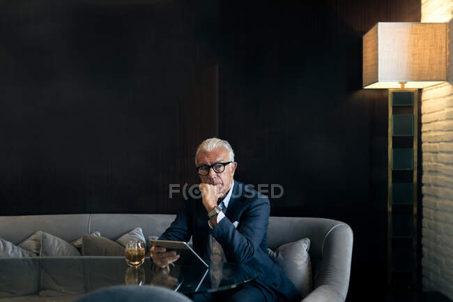 Homme d'affaires senior assis dans la table de l'hôtel en utilisant une tablette numérique, portrait — Photo de stock