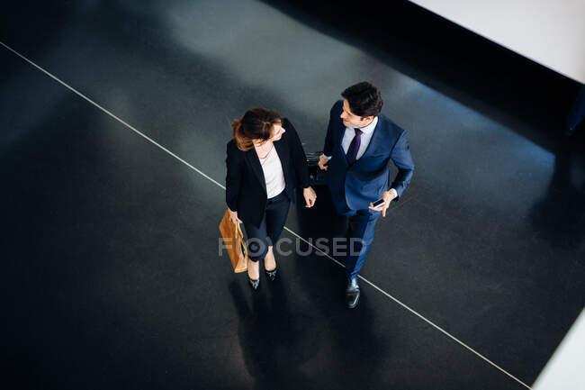 Homme d'affaires et femme d'affaires avec bagages à roues dans le bâtiment de l'hôtel — Photo de stock