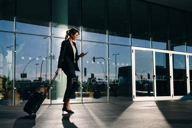 Businesswoman with wheeled luggage passing glass building, Malpensa, Milan — Stock Photo