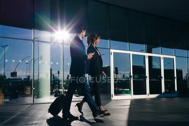 Homme d'affaires et femme d'affaires avec bagages à roues passant bâtiment en verre, Malpensa, Milan — Photo de stock