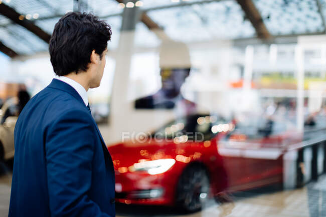 Businessman looking through glass wall at sports car in showroom — Stock Photo