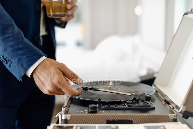 Businessman with iced drink, playing turntable in suite — Stock Photo