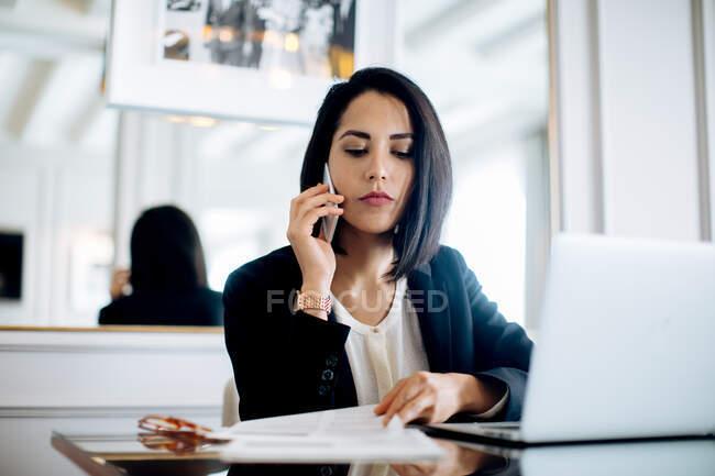 Donna d'affari che utilizza smartphone e laptop in suite — Foto stock