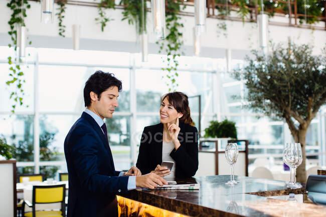 Uomo d'affari e donna d'affari che bevono al bar — Foto stock