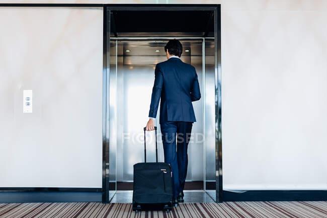 Businessman with wheeled luggage entering hotel lift — Stock Photo