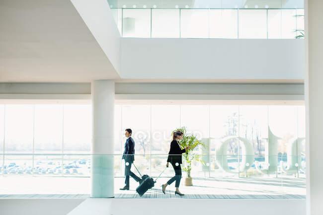 Бізнесмен і бізнесменка з колісним багажем у будинку готелю. — стокове фото