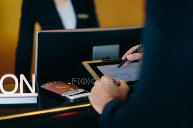 Empresario registrándose en la recepción del hotel - foto de stock