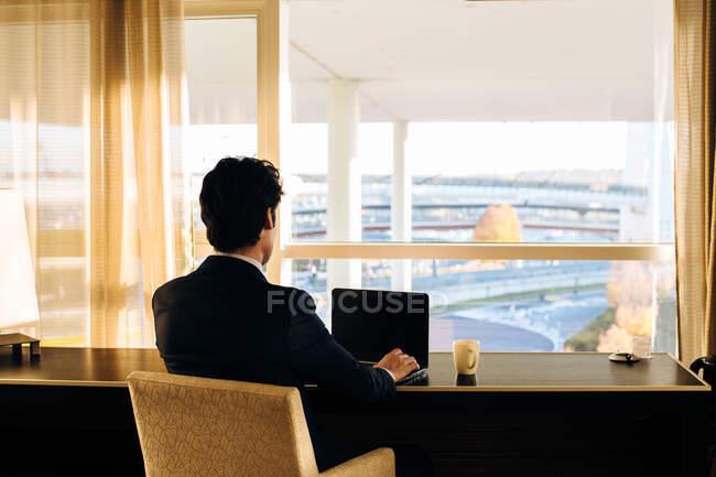 Бизнесмен использует ноутбук и смотрит в окно спальни отеля — стоковое фото