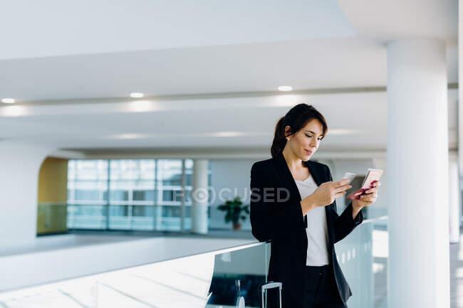 Бизнесмен, использующая мобильный телефон для электронной регистрации — стоковое фото