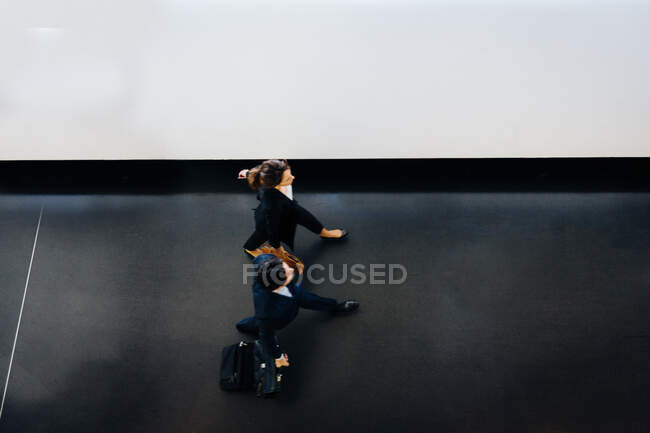 Businessman and businesswoman with wheeled luggage in hotel building — Stock Photo