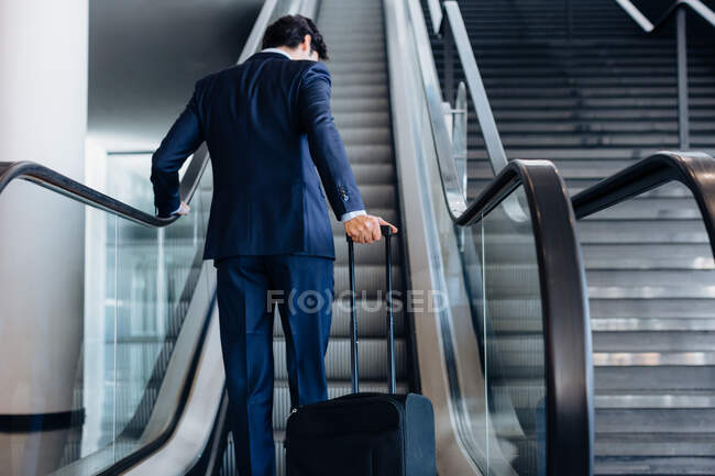 Businessman with wheeled luggage on hotel escalator — Stock Photo