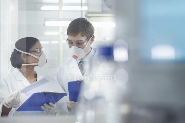 Ученые в изолированной среде в масках, работающие в исследовательской лаборатории. — стоковое фото