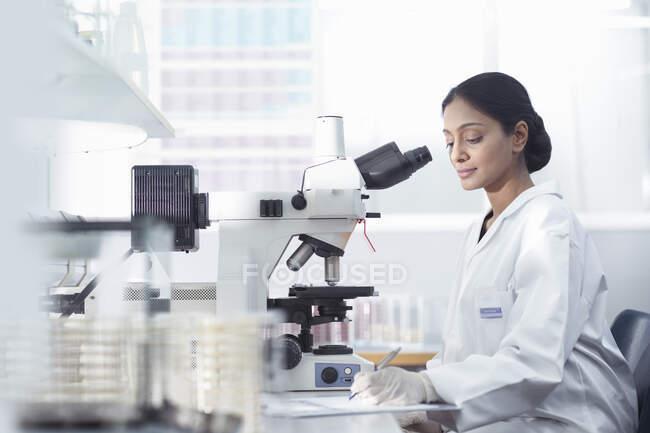 Female scientist researcher using microscope in research laboratory. — Stock Photo