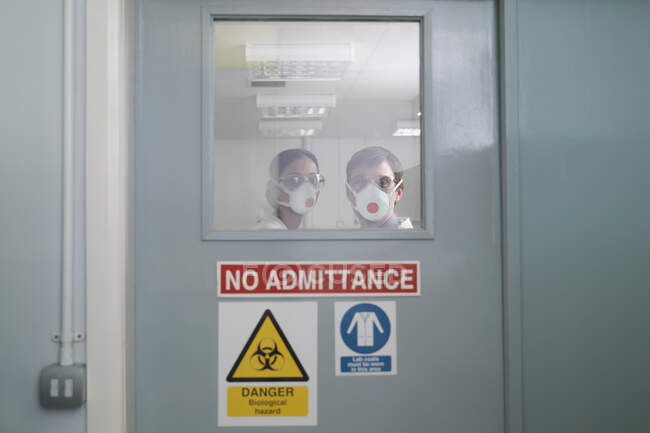 Scientists in isolation environment wearing masks with biological hazard in research laboratory. — Stock Photo