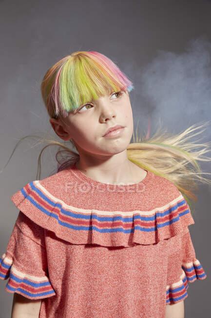 Retrato de niña con el pelo largo y colorido y franja teñida con tapa de volantes de color rosa, mirando hacia otro lado, sobre fondo gris - foto de stock