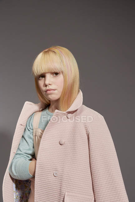 Portrait of girl with long blonde hair wearing pale pink coat, looking at camera, on grey background — Stock Photo