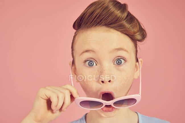 Ritratto di ragazza bruna su sfondo rosa, guardando la fotocamera sopra i suoi occhiali da sole, bocca aperta, viso scioccato e sorpreso — Foto stock
