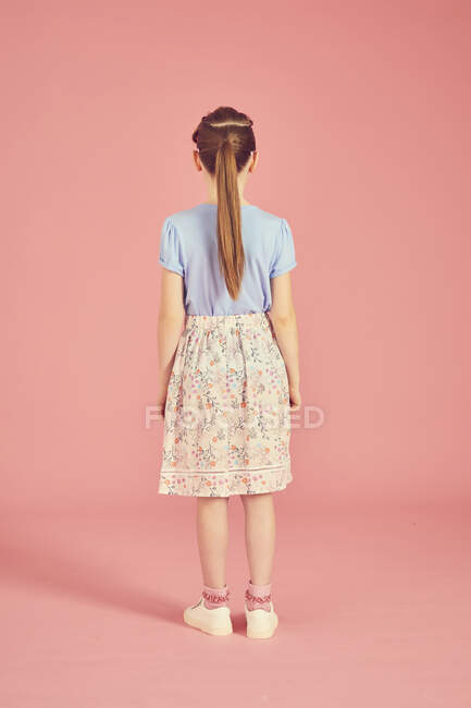 Rear view of brunette girl with ponytail wearing blue tshirt and skirt with floral pattern, on pink background. — Stock Photo