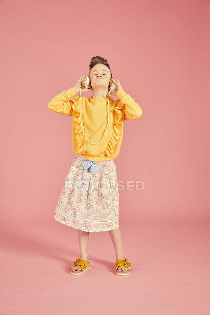 Portrait of brunette girl wearing yellow top and skirt with floral pattern holding sea shell phone, on pink background — Stock Photo