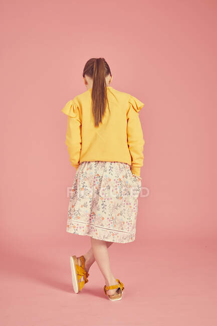 Rear view of brunette girl wearing yellow top and skirt with floral pattern on pink background, full length — Stock Photo