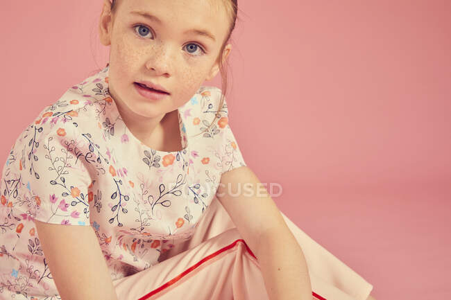 Retrato de chica morena con top floral sobre fondo rosa, mirando a la cámara - foto de stock