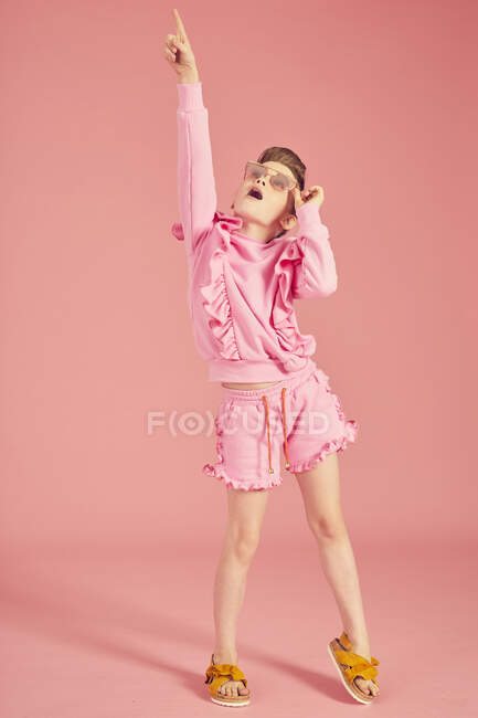 Full length, brunette girl wearing pink frilly top with shorts, wearing sunglasses on pink background and posing on camera, pointing finger up and dancing — Stock Photo