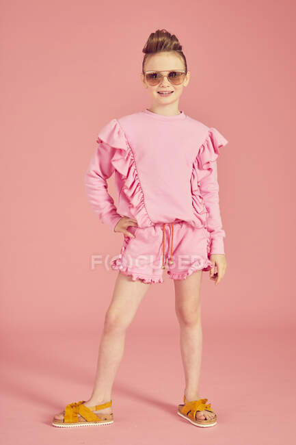 Full length, brunette girl wearing pink frilly top with shorts, wearing sunglasses on pink background and posing on camera, hand on hip — Fotografia de Stock