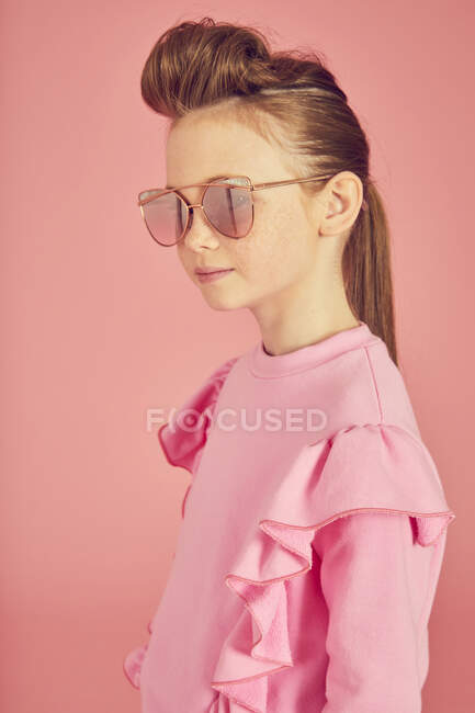 Retrato de chica morena con top de volantes rosa y gafas de sol sobre fondo rosa - foto de stock