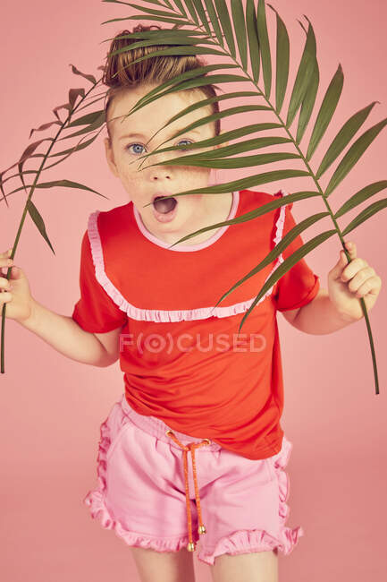 Wow, cute girl hiding behind palm leaves, studio pink background, looking at camera with opened mouth — Stock Photo