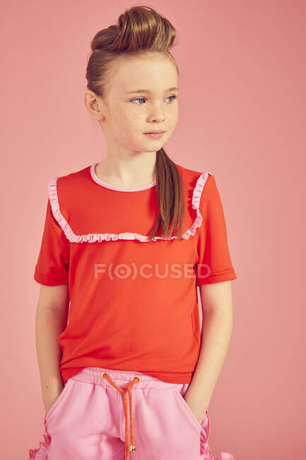 Portrait of brunette girl wearing red blouse on pink background, hands in pockets and looking away — Stock Photo