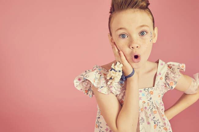 Sorpreso di ragazza bruna indossa abito frilly con motivo floreale su sfondo rosa, guardando la fotocamera, mano sulla guancia — Foto stock