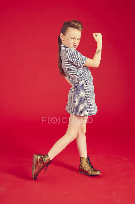Cool cute girl in dress posing against red background in studio, full length — Stock Photo