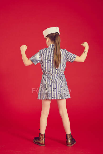 Back view of girl in dress and white sailor hat posing against red background in studio, full length — Stock Photo